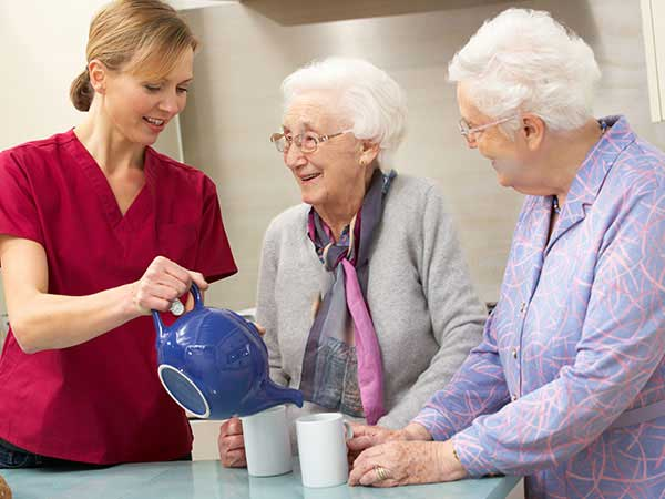 Nurse serving tea in the memory care unit